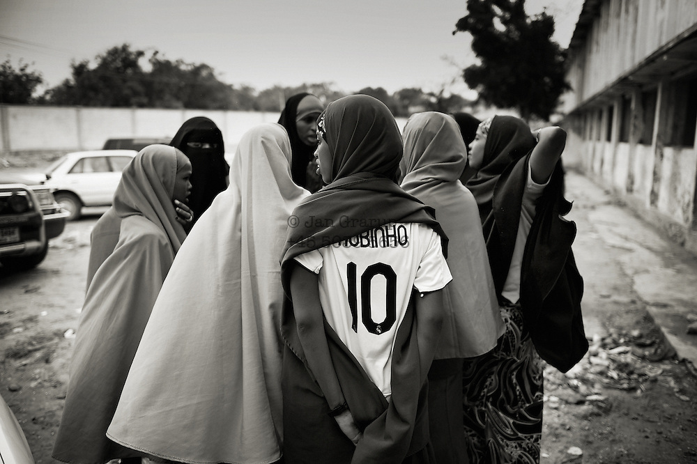 Outside the basketball court.<br /> Death or Play. Women&acute;s Basketball in Mogadishu<br /> Women's basketball? In Europa and the U.S., we take it for granted. But consider this: In Mogadishu, war-torn capital of Somalia, young women risk their lives every time they show up to play.<br /> Suweys, the captain of the Somali women&acute;s basketball team, and her friends play the sport of the deadly enemy, called America. This is why they are on the hit list of the killer commandos of Al Shabaab, a militant islamist group, that has recently formed an alliance with the terrorist group Al Qaeda and control large swathes of Somalia.<br /> <br /> Al Shabaab, who sets bombs under market stands, blows up cinemas, and stones women, has declared the female basketball players &bdquo;un-islamic&ldquo;. One of the proposed punishments is to saw off their right hands and left feet. Or simply: shoot them.<br /> <br /> Suweys&acute; team trains behind bullet-ridden walls, in the ruins of the failed city of Mogadishu &ndash; protected by heavily armed gun-men. The women live in constant fear of the islamist killer commandos. Stop playing basketball? Never, they say.<br /> Women&acute;s basketball in the world&acute;s most dangerous capital. Female basketball in Mogadishu, Somalia.<br />
