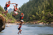 Young men leap into Oregon's Rogue River from a large boulder
