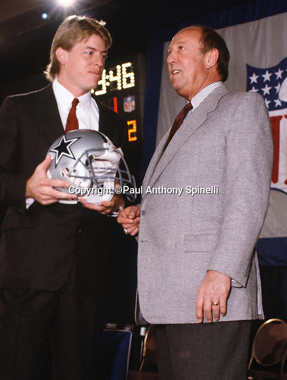 Dallas Cowboys quarterback Troy Aikman holds his new helmet and talks to NFL Commissioner Pete Rozelle on stage after being picked as the Cowboys and the number one overall NFL draft pick during the 1989 NFL Draft on April 23, 1989 in New York. (©Paul Anthony Spinelli)