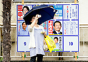 A passerby takes a photo of the ruling Liberal Democratic Party headquarters while standing in front of posters of local constituency candidates ahead of Japan's elections in Tokyo, Japan on Sunday 30 August 2009..Photographer: Robert Gilhooly