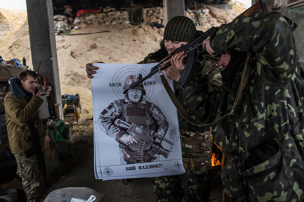 "PERVOMAISKE, UKRAINE - NOVEMBER 18, 2014: Members of the 5th platoon of the Dnipro-1 brigade, a pro-Ukraine militia, joke around after receiving target posters bearing the image of Russian actor Mikhail Porechenkov at their post underneath a bridge in Pervomaiske, Ukraine. Porechenkov came under recent criticism for appearing on television wearing protective clothing labeled ""press"" while firing a machine gun toward Ukrainian lines at the hotly-contested Donetsk airport. CREDIT: Brendan Hoffman for The New York Times"