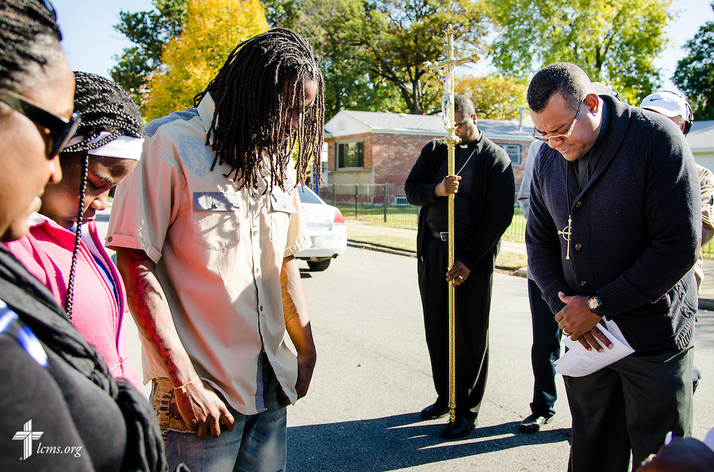 The Rev. Dwight Dickinson, right, pastor, Great Commission Lutheran Church, St. Louis, prays for College Hill residents during the LCMS Prayer & Praise Walk on Friday, Oct. 17, 2014, in the College Hill neighborhood of St. Louis. LCMS Communications/Frank Kohn