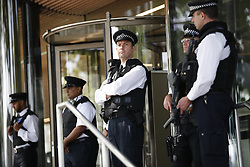 © Licensed to London News Pictures. 25/05/2017. London, UK. Police officers observe one minute silence for the victims of the Manchester Arena bombing, outside New Scotland Yard in Westminster, London on Thursday, 26 May 2017. Photo credit: Tolga Akmen/LNP