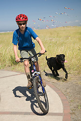 United States, Washington, Long Beach, boy (age 9) riding bicycle with dog running behind, and kites in sky.  MR