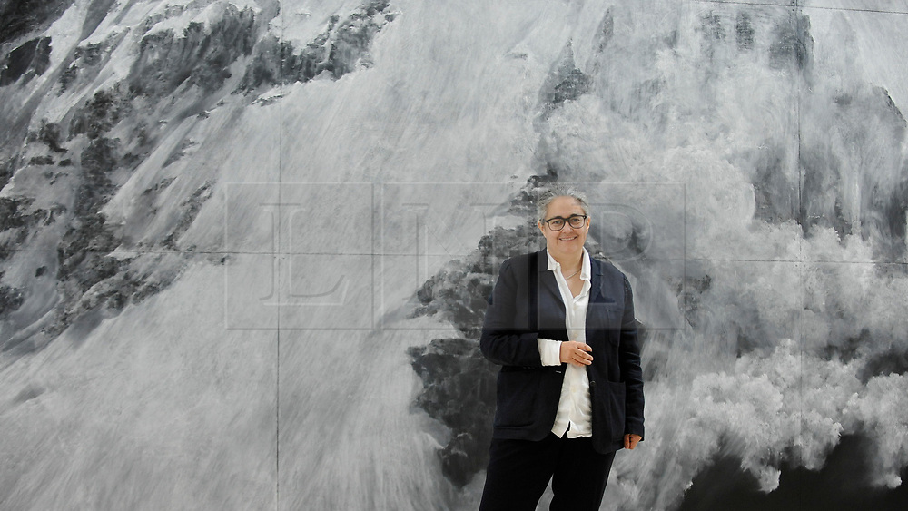 """© Licensed to London News Pictures. 14/05/2018. LONDON, UK. Tacita Dean, artist, poses with her work """"The Montafon Letter"""", 2017, in the new Gabrielle Jungels-Winkler Galleries at a photocall for the opening of the new Royal Academy of Arts (RA) in Piccadilly.  As part of the celebrations for its 250th anniversary year, redevelopment has seen the RA's two buildings, 6 Burlington Gardens and Burlington House, united into one extended campus and art space extending from Piccadilly to Mayfair.  Photo credit: Stephen Chung/LNP"""