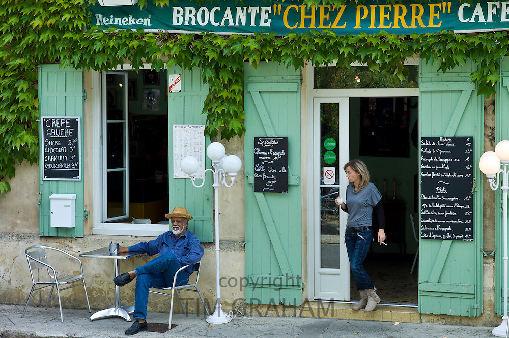 Customers at traditional French Cafe with menus in quaint town of Castelmoron d'Albret in Bordeaux region, Gironde, France