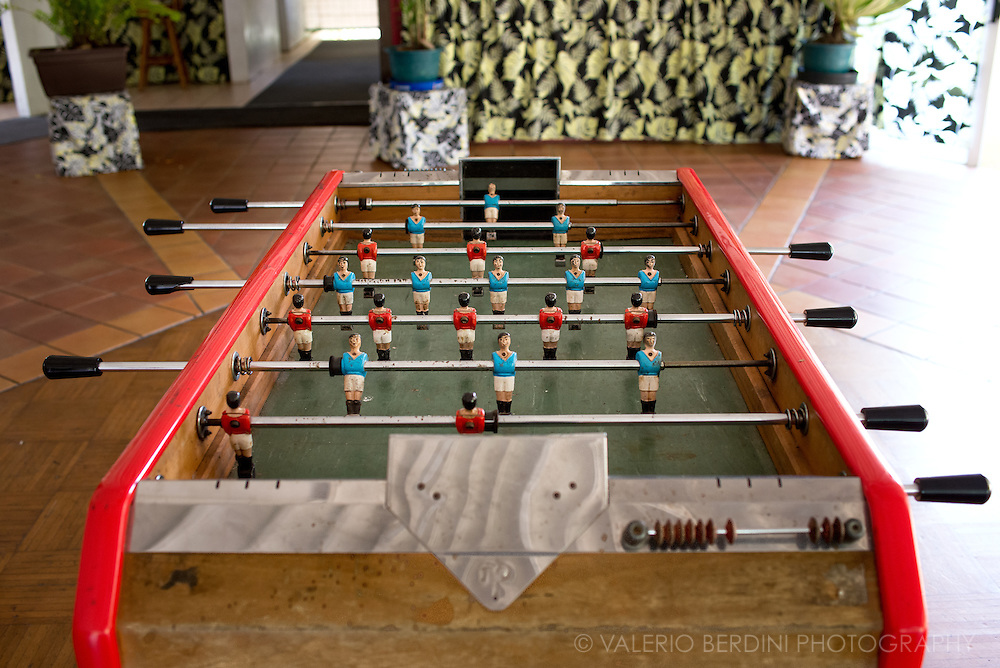An old, table football game in the hall of a hotel in the inner part of Tahiti island, far from the sea. Set in a lush vegetation within 2000 mt high mountains, there is only one road, accessible by 4X4 cars and a small restaurant for tourists arriving here with day excursions.