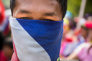 18 FEBRUARY 2014 - BANGKOK, THAILAND: An anti-government protestor wearing a Thai flag bandana as a mask waits to confront Thai riot police near Government House. Anti-government protestors aligned with Suthep Thaugsuban and the People's Democratic Reform Committee (PDRC) clashed with police Tuesday. Protestors opened fire on police with at rifles and handguns. Police returned fire with live ammunition and rubber bullets. The Bangkok Metropolitan Administration's Erawan Emergency Medical Centre reported that three civilians and a policeman were killed and 64 others were injured in the clashes between police and protesters.    PHOTO BY JACK KURTZ