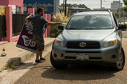Pro-life activist Keith Dalton, 28, hands out literature to a patient arriving at the Jackson Women's Health Organization clinic, on Tuesday August 19, 2014, in Jackson, Mississippi. This is the only clinic in the entire state that performs abortions. (Photo © Jock Fistick)