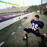 "Liberty University kicker Ben Shipps stretches at a practice at Williams Stadium.  Shipps was born was an arm deformity has been able to overcome the odds and is now kicking for the team.  ""When people say I can't do something that really pushes me and I want to prove them wrong and show them that anything can be done through the power of God."""