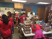Students at Oak Forest Elementary School organize food items at Manna Food Pantry.