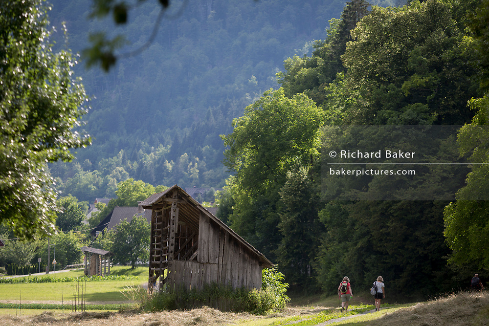 Walkers pass-by a traditional Slovenian hay rack called a toplar - or kozolec - on 18th June 2018, in Bohinjska Bela, Bled, Slovenia.
