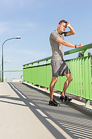 Full length of tired man wiping sweat on bridge after jogging