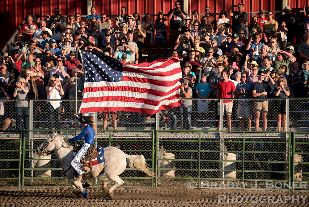 Teton County Lady in Waiting Claire Andrews rides through the rodeo arena with an American flag before the Fourth of July rodeo Tuesday evening.