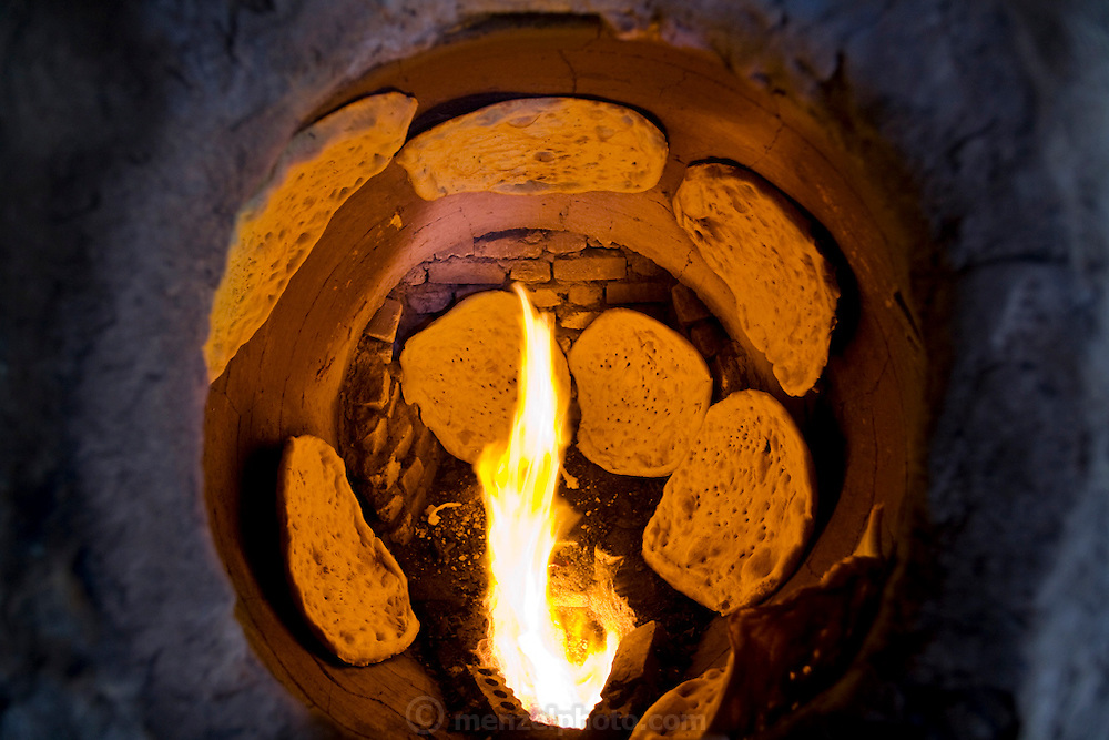 Bread bakes inside circular ovens at Akbar Zareh's bakery in the city of Yazd, Iran. (Akbar Zareh is featured in the book What I Eat: Around the World in 80 Diets.) The son of a baker, Zareh began working full-time at age 10 and regrets that he didn't attend school and learn how to read and write. By working 10 hours a day, every day of the week, he has sent his four children to school so they don't have to toil as hard as he does. The product of his daily labor is something to savor?his fresh, hot loaves are as mouthwatering and tasty as any in the world. After baking in the tandoor clay ovens (at left), most of the rounds of fresh bread are dried and broken into bits.