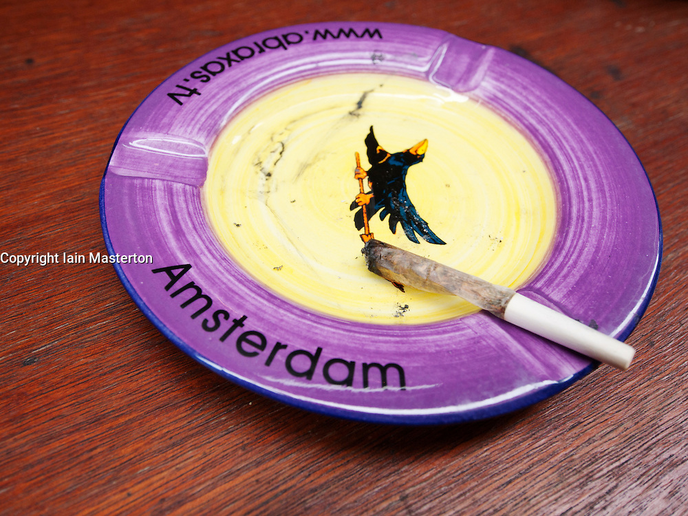 Detail of joint of cannabis and cup of coffee at Amsterdam coffeeshop in The Netherlands