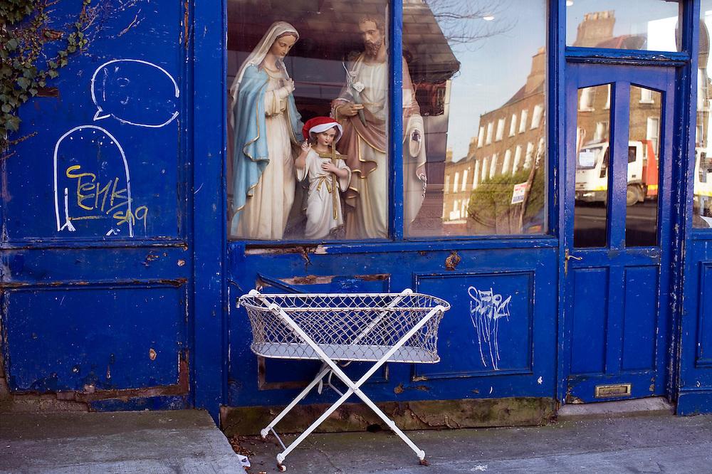 Ireland, Dublin. A nativity set stare down from a shop window at an abandoned crib. Dublin, Ireland