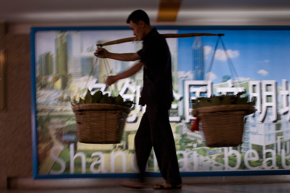Asia, China, Shanghai, Man carrying bundles walks past illuminated signboard showing Shanghai skyline in tunnel leading to People's Square Metro subway station