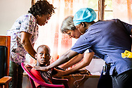 Bonnie Hartman, a member of Faith Lutheran Church, Godfrey, Ill., works with counterpart nurses from Sierra Leone as they prepare a child for vitals on the first day of the LCMS Mercy Medical Team on Monday, May 7, 2018, in the Yardu village outside Koidu, Sierra Leone, West Africa. LCMS Communications/Erik M. Lunsford