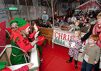 """Harper and Harry Meehan get surprised by the """"ELF in the box"""" as they work their way through Laconia's Christmas Village during opening night last evening.  (Karen Bobotas/for the Laconia Daily Sun)"""
