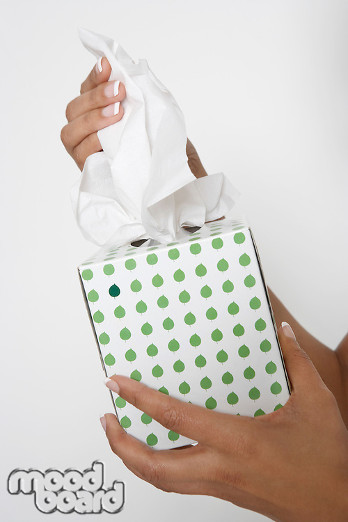 Woman holding box of tissues, close-up of hands