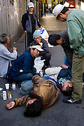In a market street of Kamagasaki, homeless day laborers alert over one of them who is unconsious. The guy eventualy recovered but it was said that three other homeless people died that night because of the cold weather.