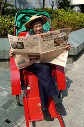 Chinese man in rickshaw reading Financial Times newspaper in Hong Kong China