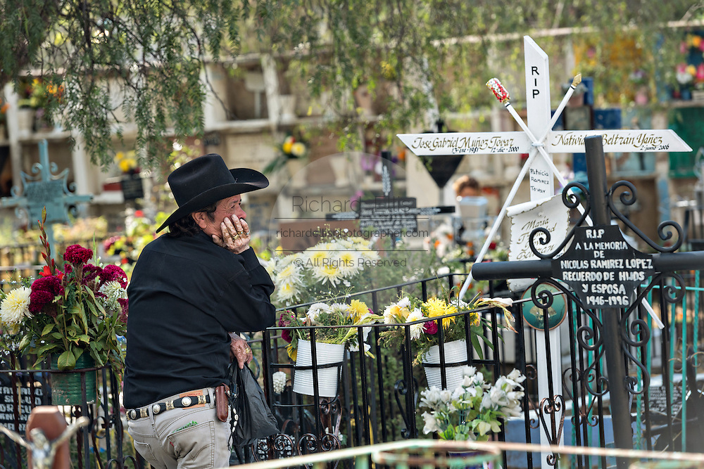 A Mexican man pauses at the grave of a relative in the Nuestra Señora de Guadalupe cemetery during the Day of the Dead festival November 1, 2016 in San Miguel de Allende, Guanajuato, Mexico. The week-long celebration is a time when Mexicans welcome the dead back to earth for a visit and celebrate life.
