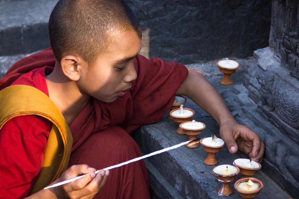 A buddhist novice lights butter lamps at Swayambhunath stupa, also known as the Monkey Temple, in Kathmandu, Nepal.