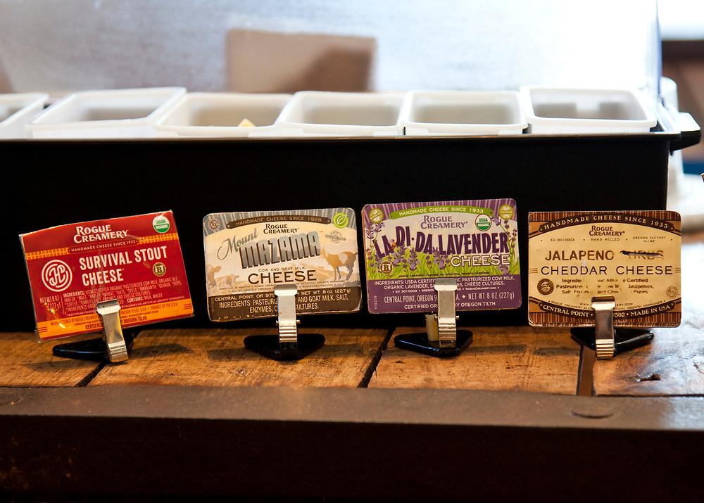 Artisan cheese labels at tasting bar, Rogue Creamery Cheese Shop, Medford, Oregon.