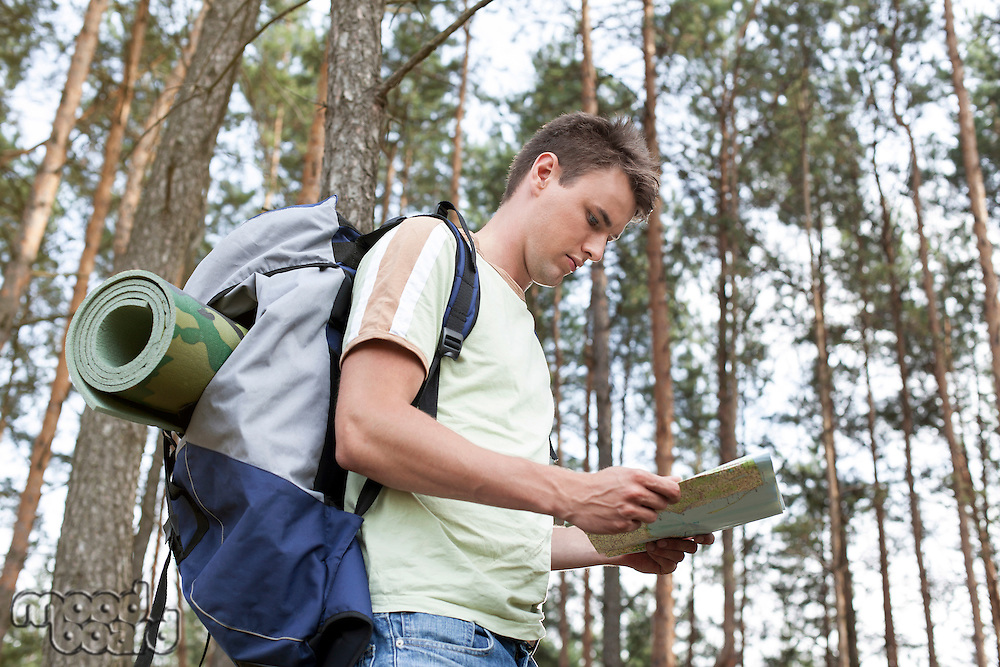Side view of young man with backpack reading map in woods