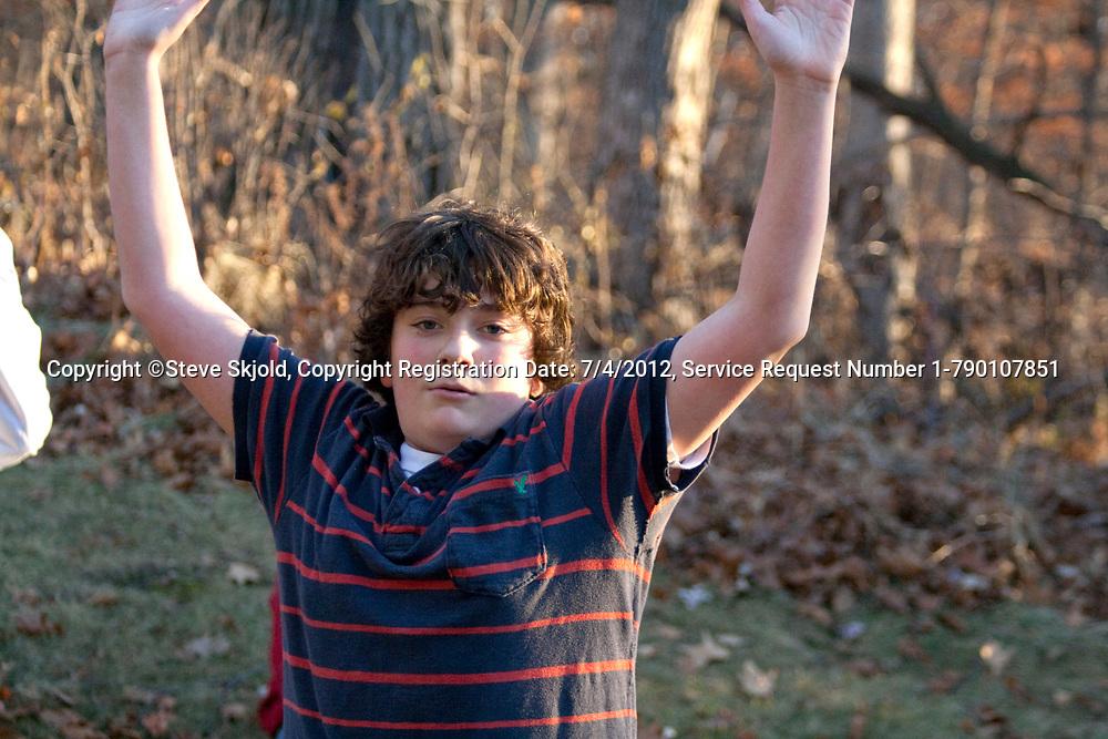 Teenage boy age 13 blocking pass in a backyard touch football game. Champlin Minnesota MN USA