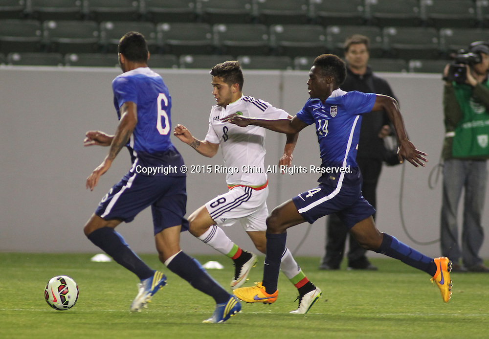 Mexico's Uvaldo Luna Martinez #8 actions against United States' Christian Dean #6 and Fatai Alashe #14 during a men's national team international friendly match, April 22, 2015, at StubHub Center in Carson, California. United States won 3-0.  (Photo by Ringo Chiu/PHOTOFORMULA.com)