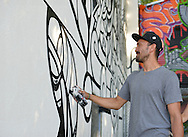 """Huntington, New York, U.S. 24th August 2013. MASPAZ, world renowned street artist FEDERICO FRUM from Washington DC, is painting black and white graffiti on the back of the Huntington Arts Council building, during the the art event """"Off the Walls"""" Block Party, by SPARKBOOM, a project the council created to help emerging artists, showcase talents, and help its artistic family network. Mas Paz was born in Bogata Columbia and adopted from an orphanage when he was one; and he founded a charitable foundation to help the orphanage and other causes."""