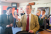 © Licensed to London News Pictures. 29/04/2014. Slough, UK. Nigel Farage holds up a UKIP beer mat in Lynchpin pub in Slough.  NIGEL FARAGE leader of UKIP in Slough today 29 April 2014 to congratulate local activists on more than doubling the candidates the party will field in local elections. Photo credit : Stephen Simpson/LNP
