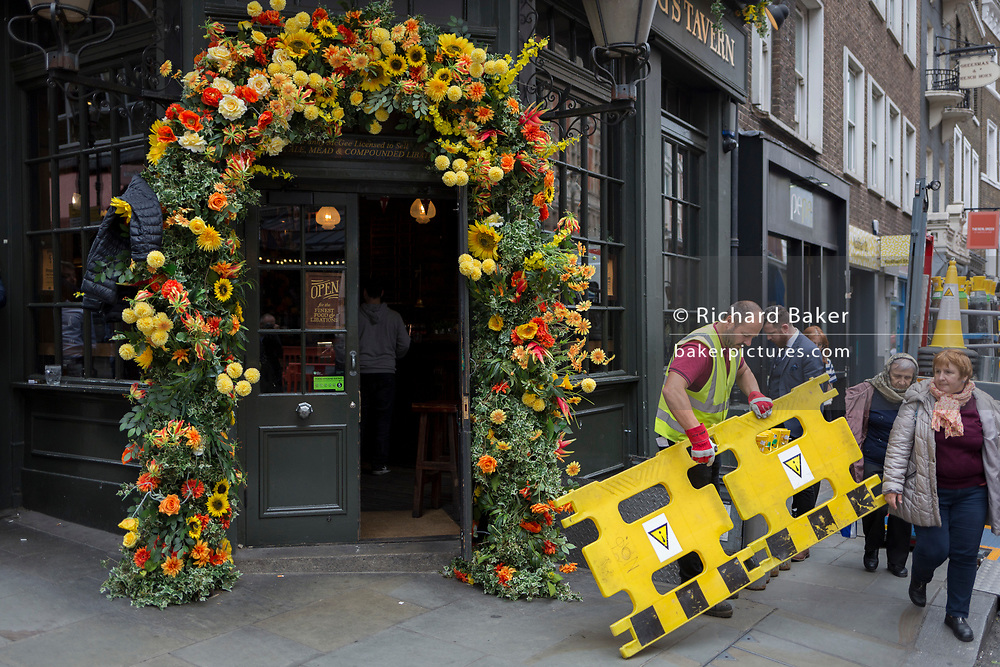 Alongside a floral display over the doorway of the Angel & Crown pub, a delivery man attends to the delivery of new stock to its cellar on St. Martin's Lane,  on 15th June 2019, in London, England.