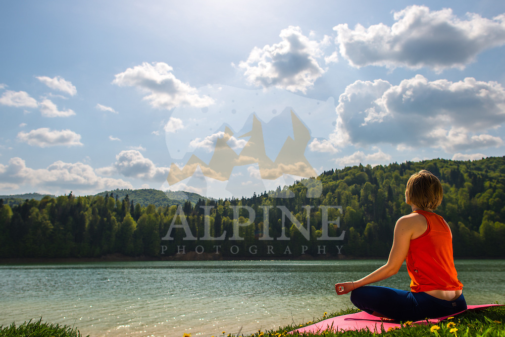 A female athlete, as seen practising yoga positions by the lake of Vidraru on a sunny day in the dense, Summer forests of Agre?, Romania.