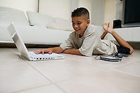 Boy Using Laptop on Floor in living room ground view