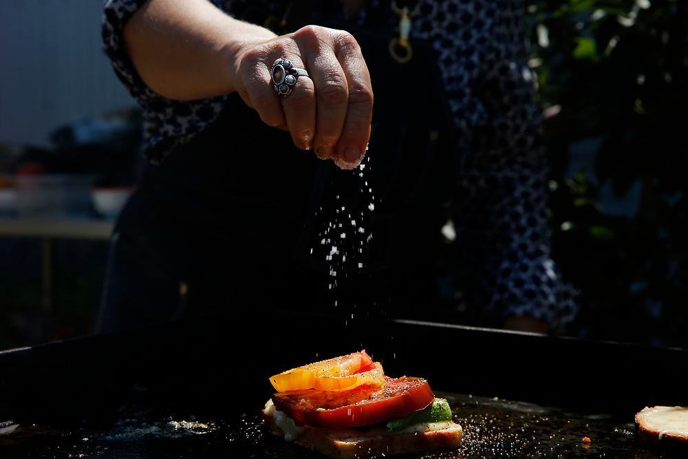 Kendra Kolling seasons her The Works sandwich at The Barlow on Tuesday, Aug. 22, 2017, in Sebastopol, Calif.