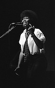 Joan Armatrading singing with eyes wide open showing teeth
