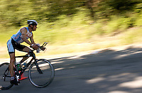 JEROME A. POLLOS/Press..An Ironman competitor speeds around a curve along Riverview Drive.