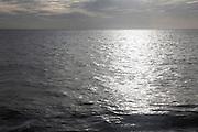 Sunshine falling on expanse of grey sea water, North Sea, Suffolk, England