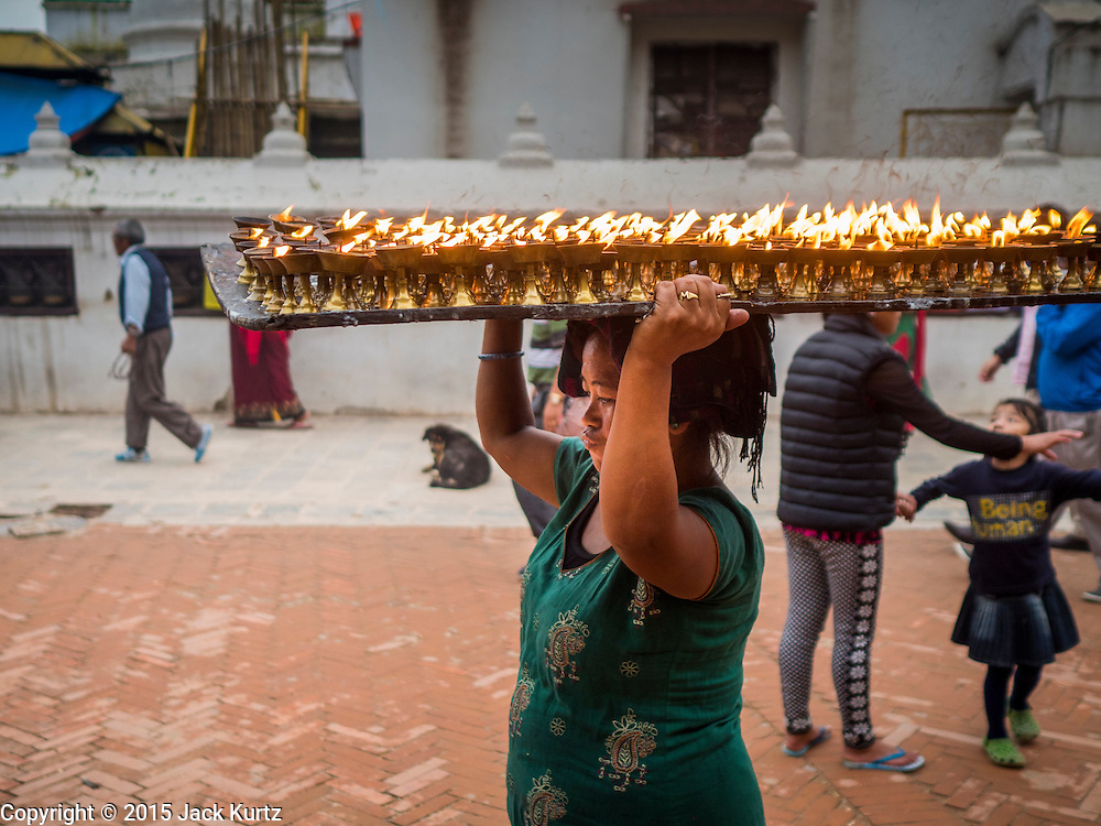 31 JULY 2015 - KATHMANDU, NEPAL: A woman carries a tray of butter lamps across the plaza around Bodhnath Stupa during the full moon procession around the stupa. Bodhnath Stupa in the Bouda section of Kathmandu is one of the most revered and oldest Buddhist stupas in Nepal. The area has emerged as the center of the Tibetan refugee community in Kathmandu. On full moon nights thousands of Nepali and Tibetan Buddhists come to the stupa and participate in processions around the stupa. The stupa was heavily damaged in the earthquake of 25 April 2015 and people are no longer allowed to climb on the stupa, now they walk around the base and pray with butter lamps.   PHOTO BY JACK KURTZ