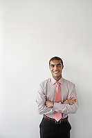 Business man standing against wall in office portrait