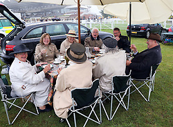 Racegoers cover up during their picnic lunch at a wet and windy opening day of Glorious Goodwood in the UK, Tuesday, 30th July 2013 <br /> Picture by Stephen Lock / i-Images
