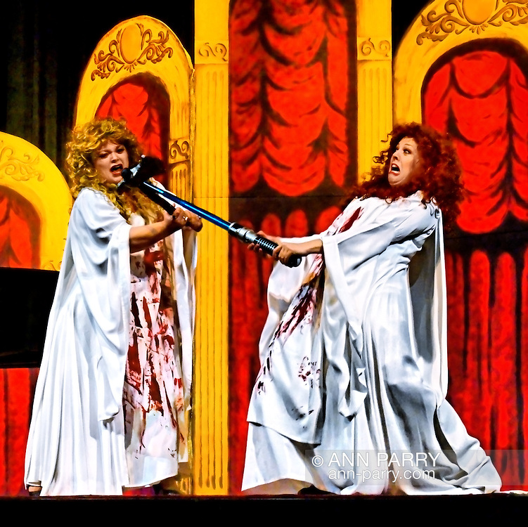 """MERRICK, NY - February 21: Duelling Divas concert with sopranos Birgit Firavante and Wendy Reynolds and pianist Heather Coltman in bloody fight, one using sword to block hatchet swung at her face, in Mad scene from Donizetti's """"Lucia di Lammermoor"""" in comic opera concert presented by Merrick Bellmore Community Concert Association on February 21, 2010 at Merrick, NY."""