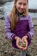 A girl with braces holds bits of sea glass in her hands at Glass Beach in Fort Bragg, Mendoino County, northern California. Model released.