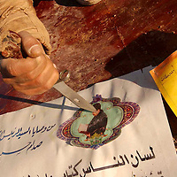 ERBIL, NORTHERN IRAQ - MARCH 29:  A Kurdish Peshmerga Special Branch Fighter is sticking a knifeinto a Saddam Hussein Poster at  the Sherawa checkpoint which was abandoned as the Iraqi army retreated towards Kirkuk.  Peshmergas are ready to take the city in Northern Iraq in cooperation with recently landed US forces.<br />
