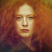 Close-up portrait of female youth withfreckles, red curly hair and piercing green eyes.
