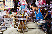 """13 FEBRUARY 2014 - BANGKOK, THAILAND: A market vendor sets up a display of rice in Khlong Toei Market in Bangkok. The Thai government instituted a """"rice pledging scheme"""" after the election in 2011. The government agreed to buy farmers' rice crops at above market prices then planned to warehouse the rice and sell it on international markets when prices recovered. At the same time, India and Vietnam started to export large quantities of rice and the Thai government fell short of funds to pay for rice it had already purchased from farmers. Many farmers have not been paid for rice grown in 2013 and some of the rice in the Thai warehouses is allegedly rotting. Thailand has fallen from number 1 rice exporter in the world to number 3 and several government to government contracts the Thais signed with rice importing countries (like China) have been cancelled. Farmers, once key supporters of the government are now joining anti-government protests in Bangkok and occupying government ministries including the Ministry of Commerce.    PHOTO BY JACK KURTZ"""